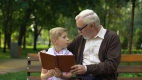 Farfarläsebok med sonsonen som tillsammans studerar, kunskap av världen arkivfilmer