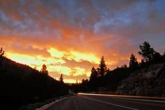 Fari che scorrono giù la strada principale con un tramonto montagnoso nei precedenti immagini stock libere da diritti