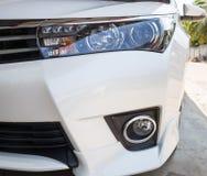 Fari del primo piano dell'automobile bianca moderna con luce del giorno del LED Fotografie Stock Libere da Diritti