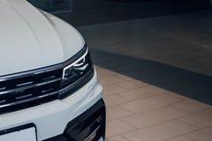 Fari del primo piano di un'automobile bianca moderna di colore Dettaglio sul fanale anteriore di un'automobile fotografia stock libera da diritti