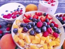 Farina d'avena, albicocca, fragola, yogurt naturale antiossidante su fondo di legno fotografie stock libere da diritti