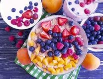 Farina d'avena, albicocca, fragola, yogurt naturale su fondo di legno fotografia stock