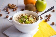 Farina d'avena con i dadi e frutti per la prima colazione Fotografie Stock