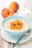 Farina d'avena con le pesche caramellate in una ciotola, yogurt per la prima colazione Immagine Stock