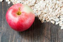 Farina d'avena cruda con l'intera mela rossa Fotografia Stock