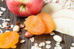 Farina d'avena cruda con l'intera mela rossa, l'albicocca secca ed i dadi Immagine Stock Libera da Diritti