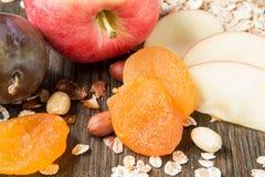 Farina d'avena cruda con l'intera mela rossa, l'albicocca secca ed i dadi Fotografie Stock Libere da Diritti