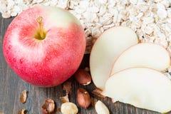 Farina d'avena cruda con l'intere mela ed arachide rosse Immagini Stock