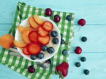 farina d'avena, fragola, mirtillo, ciliegia sana, albicocca antiossidante su un fondo di legno blu fotografia stock