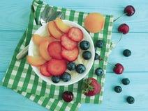 farina d'avena, fragola, mirtillo, ciliegia sana dell'alimento, albicocca antiossidante su un fondo di legno blu immagini stock