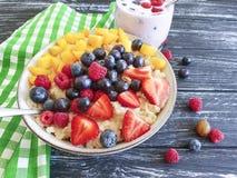Farina d'avena, fragola, naturale casalingo nutriente del yogurt antiossidante organico del mirtillo su un fondo di legno nero immagini stock