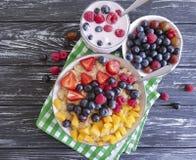 Farina d'avena, fragola sana del lampone del yogurt di mirtillo su un antiossidante di legno del fondo immagine stock