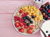 farina d'avena, fragola, yogurt antiossidante del mirtillo sano del dessert dell'albicocca del lampone su un fondo di legno rosa fotografie stock