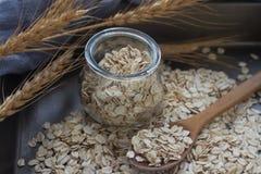 Farina d'avena nutriente saporita in un barattolo di vetro, in un cucchiaio di legno e nelle spighe del granoturco su fondo scuro Fotografia Stock Libera da Diritti