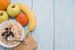 Farina d'avena sana della prima colazione con l'uva passa in ciotola bianca Due mele verdi, banane Vista superiore piana Fotografia Stock Libera da Diritti