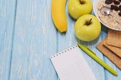 Farina d'avena sana della prima colazione con l'uva passa in ciotola bianca Due mele verdi, banane Vista superiore piana Immagine Stock