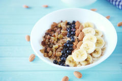 Farina d'avena sana della prima colazione con la banana, dadi della mandorla, mirtilli Fotografia Stock Libera da Diritti