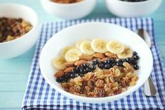 Farina d'avena sana della prima colazione con la banana, dadi della mandorla, mirtilli Immagini Stock Libere da Diritti