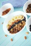 Farina d'avena sana della prima colazione con la banana, dadi della mandorla, mirtilli Fotografie Stock Libere da Diritti