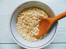 farina d'avena in una ciotola ed in un cucchiaio di legno su una tavola bianca Immagini Stock Libere da Diritti