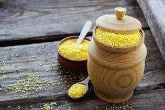 Farina di granoturco organica cruda della polenta in una ciotola di legno Immagine Stock