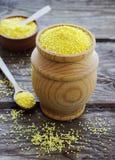 Farina di granoturco organica cruda della polenta in una ciotola di legno Fotografia Stock