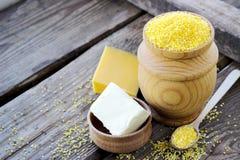 Farina di granoturco organica cruda della polenta in una ciotola di legno Immagine Stock Libera da Diritti