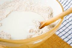 Farina, latte e un cucchiaio in una ciotola Immagine Stock