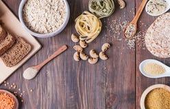 Farina, pane, pasta e lenticchie asciutte ed altri ingredienti sulla tavola di legno immagine stock