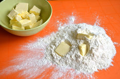 Farina spilled out on orange silicone mat next to bowl full of butter.  Stock Image