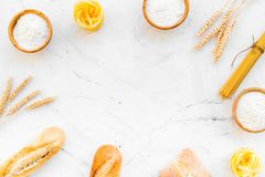 Farinaceous food. Fresh bread and raw pasta near flour in bowl and wheat ears on white stone background top view copy. Farinaceous food. Fresh bread and raw stock photos