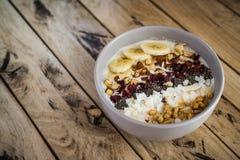 Farine d'avoine avec des bananes, canneberge, graines de chia, lambeaux de noix de coco, alm Images stock