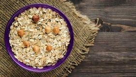 Farine d'avoine avec les noisettes nuts Farine d'avoine sur une table en bois oatmeal photographie stock libre de droits