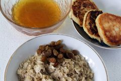 Farine d'avoine chaude de petit déjeuner avec les raisins secs et le miel images stock