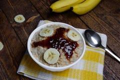 Farine d'avoine dans une belle cuvette blanche sur un fond en bois chaud avec des tranches de bananes et de confiture Images stock