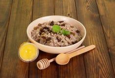 Farine d'avoine de cuvette avec des raisins secs, miel, cuillères sur le fond en bois foncé Photo stock