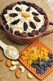 Farine d'avoine en plat, cuillère, raisins secs, anarcadiers et amandes en céramique dessus Images stock
