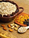 Farine d'avoine en plat, cuillère, raisins secs, anarcadiers et amandes en céramique Photo libre de droits