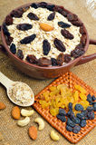 Farine d'avoine en plat, cuillère, raisins secs, anarcadiers et amandes en céramique dessus Image libre de droits