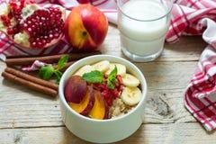 Farine d'avoine saine de petit déjeuner avec la banane, la pêche, la nectarine et la grenade avec de la cannelle Image libre de droits