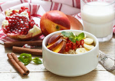 Farine d'avoine saine de petit déjeuner avec la banane, la pêche, la nectarine et la grenade avec de la cannelle Images stock