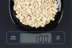 Farine d'avoine sur l'échelle de cuisine Image stock
