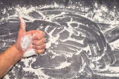 Farine de blé sur la surface de fonctionnement grise avec la main et les pouces masculins  Photo libre de droits