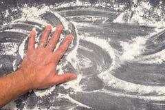 Farine de blé sur la surface de fonctionnement grise essuyée loin avec la main masculine Photo stock