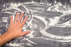 Farine de blé sur la surface de fonctionnement grise essuyée loin avec la main masculine Images stock