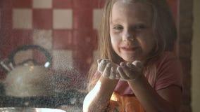 Farine de soufflement de jeune fille dans la cuisine clips vidéos