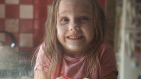 Farine de soufflement de jeune fille dans la cuisine banque de vidéos