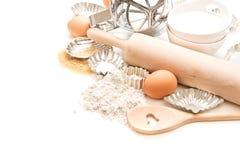 Farine, oeufs, sucre, goupille et coupeurs de biscuit sur le blanc Photographie stock libre de droits