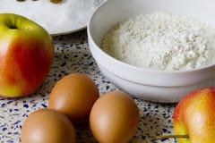 Farine, sucre, raisins secs, oeufs et pommes pour les pâtisseries faites maison Photos stock