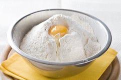 Farinha branca e ovo na bacia imagem de stock royalty free
